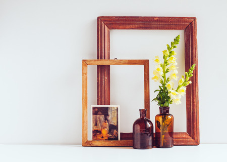 living thing: Vintage home decor, two glass brown bottles with flowers, old wooden frames and a postcard on a white background.