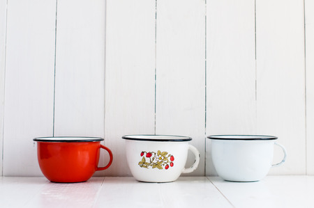 three shelves: Three bright colorful enameled mugs on white painted wooden table, rustic kitchenware and decor, vintage kitchen background