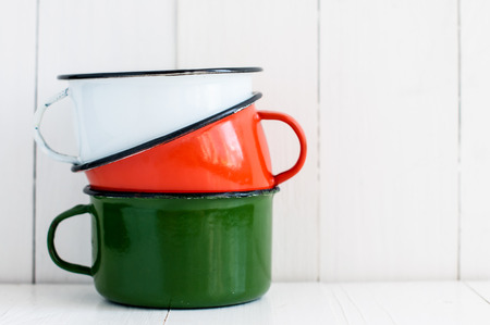 A stack of three bright colorful enameled mugs on white painted wooden table, kitchenware and decor, rustic vintage kitchen background photo