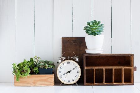 ビンテージの家の装飾: 古い木製の箱、室内用植物、ホワイト木製ボード、レトロなインテリアに目覚まし時計です。