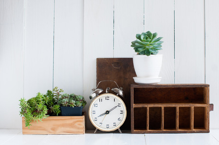 Home Decoration: Vintage home decor: old wooden boxes, houseplants, alarm clock on white wooden board, retro home interior.