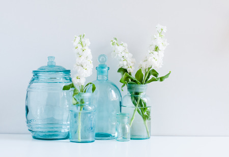 Vintage home decor background, white matthiola flowers in different blue glass bottles vases and antique jars on a shelf by the wall Banque d'images
