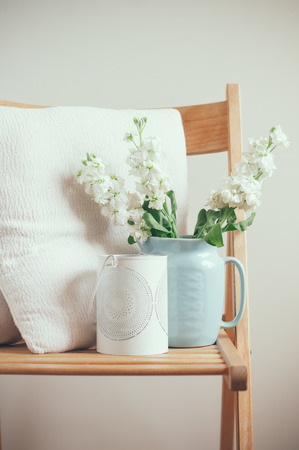 Vintage home decor, white matthiola flowers in a blue jug on a chair with pillows by the wall