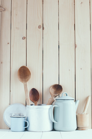 country kitchen: Home kitchen still life: Vintage coffee pot, enamel mugs and antique rustic wooden spoons on a barn wall background, soft pastel colors.