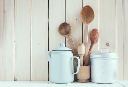 Küche zu Hause noch Leben: Vintage Kaffeekanne, Emaille-Becher und antiken rustikalen Holzlöffel auf einer Scheune Wand Hintergrund, weiche Pastellfarben. Lizenzfreie Bilder