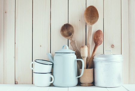Home kitchen still life: Vintage coffee pot, enamel mugs and antique rustic wooden spoons on a barn wall background, soft pastel colors. photo