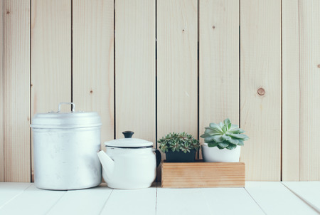 Vintage home arrangement, summer plants and enamelware on a barn wall background, soft pastel colors. photo