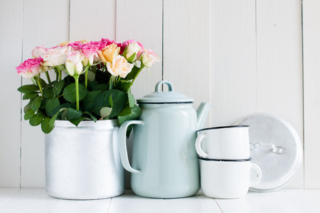 arrangement: Vintage home arrangement, summer flowers and enamelware on a barn wall background, soft pastel colors.