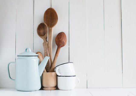 Home kitchen still life: Vintage coffee pot, enamel mugs and antique rustic wooden spoons on a barn wall background, soft pastel colors.