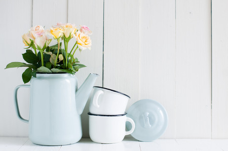 decoration work: Vintage home arrangement, summer flowers and enamelware on a barn wall background, soft pastel colors.