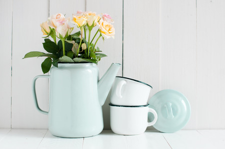 Vintage home arrangement, summer flowers and enamelware on a barn wall background, soft pastel colors. photo
