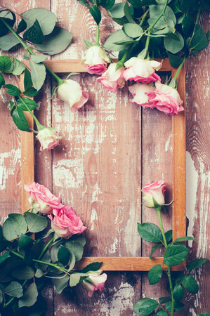 Bouquet of pink roses and a wooden frame on old board background, vintage color tinting