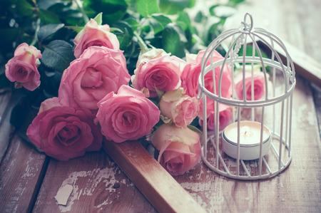 Boeket van roze rozen, houten frame en een brandende kaars in een witte decoratieve vogelkooi op oude bord achtergrond, vintage decor en kleur verven
