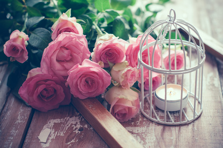 decor: Bouquet of pink roses, wooden frame and a burning candle in a white decorative bird cage on old board background, vintage decor and color tinting Stock Photo