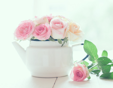 Bouquet of yellow and pink roses in a white enameled vintage teapot in bright sunlight on a white wooden table, home decor, pastel colors photo