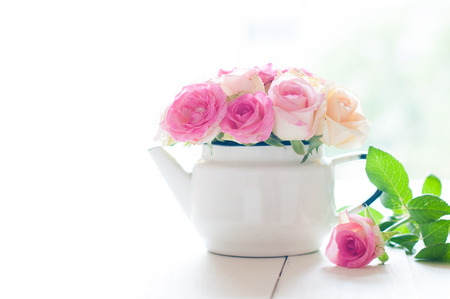 yellow tea pot: Bouquet of yellow and pink roses in a white enameled vintage teapot in bright sunlight on a white wooden table, rustic home decoration background Stock Photo