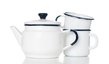 Home kitchenware, vintage enameled kettle and mugs isolated on white background photo