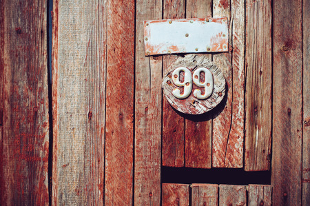99: Texture of brown wooden planks, barn wall and 99 number, abstract rustic background Stock Photo