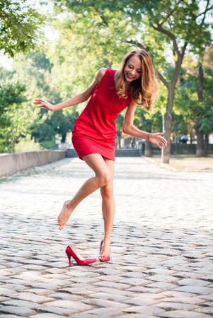tacones rojos: Joven y bella mujer delgada en una luz de fondo por la mañana en una calle vacía de la ciudad, dama en vestido rojo y zapatos de tacón alto se divierte, dejó caer su zapato Foto de archivo