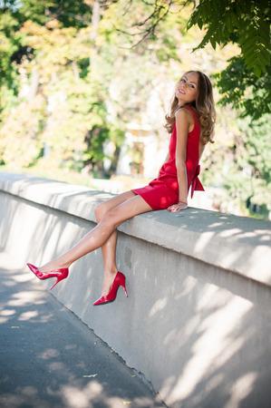 tacones rojos: Atractivo joven mujer delgada en una calle de la ciudad, señora en vestido rojo y zapatos de tacón alto se divierte, sentado, sonriendo Foto de archivo
