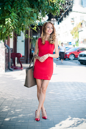 Beautiful young slim woman in a street of European city, business lady in red dress and high heels laughing. Stock Photo - 31729391