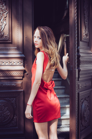 Attractive young woman in a open back red dress and heels in front of the old antique wooden door on the European city street photo