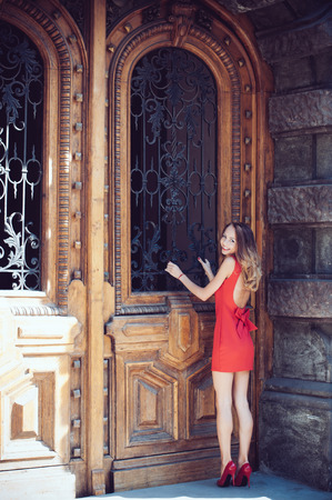 Attractive young woman in a open back red dress and heels in front of the old antique wooden door looking inside, on the European city street photo