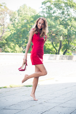 Beautiful young slim woman on an empty city street, lady in red dress and high heels has fun, dancing barefoot without her shoes, smiling