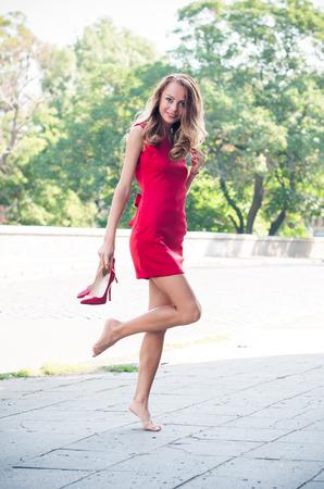 tacones rojos: Joven y bella mujer delgada en una calle vacía de la ciudad, señora en vestido rojo y zapatos de tacón alto se divierte, bailando descalza y sin zapatos, sonriendo Foto de archivo