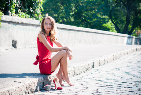 Beautiful young slim woman on an empty city street, lady in red dress and high heels has fun, sitting on a pavement barefoot without her shoes, smiling Фото со стока