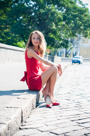 Beautiful young slim woman on an empty city street, lady in red dress and high heels has fun, sitting on a pavement barefoot without her shoes, smiling Stock Photo