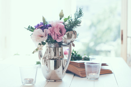 arrangement: Summer bouquet of purple and pink eustomas in an antique coffee pot on white wooden table, vintage style, holiday and wedding floral decorations