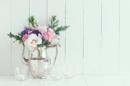 Summer bouquet of purple and pink eustomas in an antique coffee pot on a white wooden board, vintage style, holiday and wedding floral background, pastel colors Stock Photo