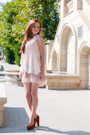 long red hair woman: Portrait of attractive red-haired girl with freckles in the summer beige dress standing on a sunny street Stock Photo
