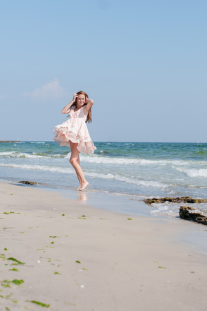 Beautiful red-haired girl in the summer beige dress dancing alone on a beach photo