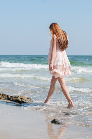 hair back: Beautiful red-haired girl in the summer beige dress walking along the beach Stock Photo