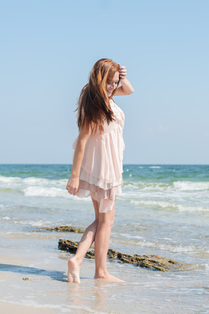 Beautiful red-haired girl with freckles in the summer beige dress walking along the beach photo
