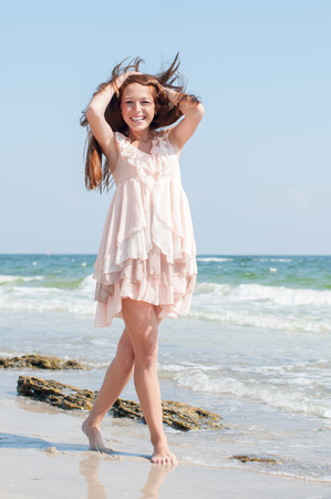 Beautiful red-haired girl with freckles in the summer beige dress dancing alone with the wind on a beach photo