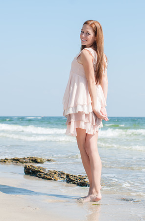 freckles: Beautiful red-haired girl with freckles in the summer beige dress walking along the beach