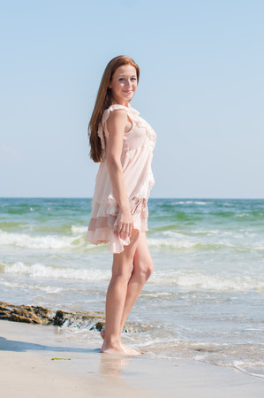 redhaired: Beautiful red-haired girl with freckles in the summer beige dress walking along the beach