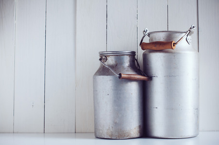 Two old vintage aluminum milk cans, painted white wooden board, rustic background photo