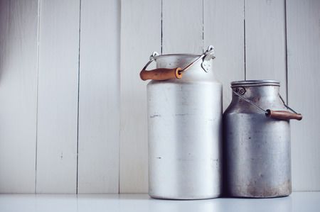 milk containers: Two old vintage aluminum milk cans, painted white wooden board, rustic background Stock Photo