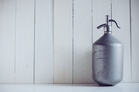 seltzer: An old vintage aluminum siphon, antique seltzer soda bottle, painted white wooden board, rustic background Stock Photo