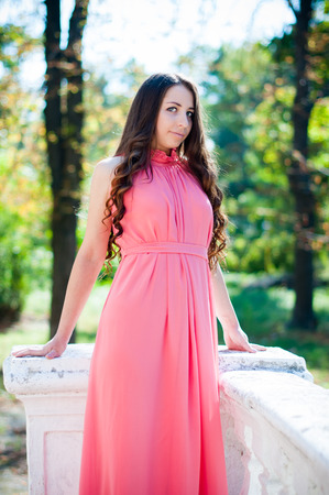 maxi dress: Pretty young girl with long hair in a park, a bridesmaid in a pink maxi dress. Stock Photo