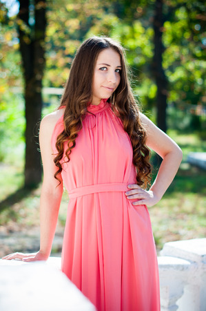 maxi: Pretty young girl with long hair in a park, a bridesmaid in a pink maxi dress. Stock Photo