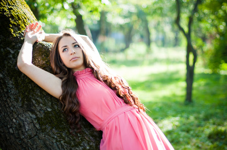 maxi dress: Pretty young girl in a pink dress with long hair posing in the park near the tree, forest fairy