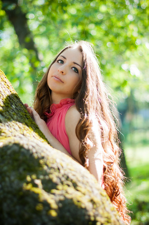 Pretty young girl in a pink dress with long hair posing in the park near the tree, portrait of a forest fairy