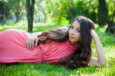 maxi dress: Pretty young girl in a pink dress with long hair posing in the park laying in a grass, forest fairys portrait Stock Photo