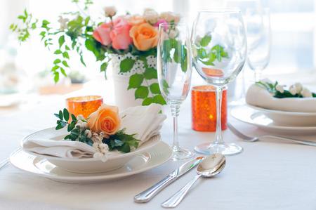 色とりどりの花、カトラリー、キャンドルとエレガントなお祝いテーブル設定。結婚式のテーブル デコレーション。