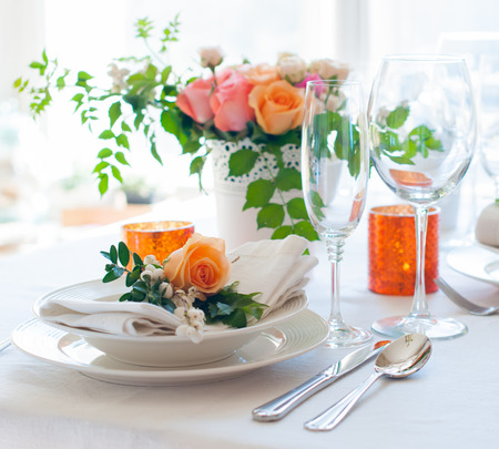 Elegant festive table setting with colorful flowers, cutlery, candles. Wedding table decoration.
